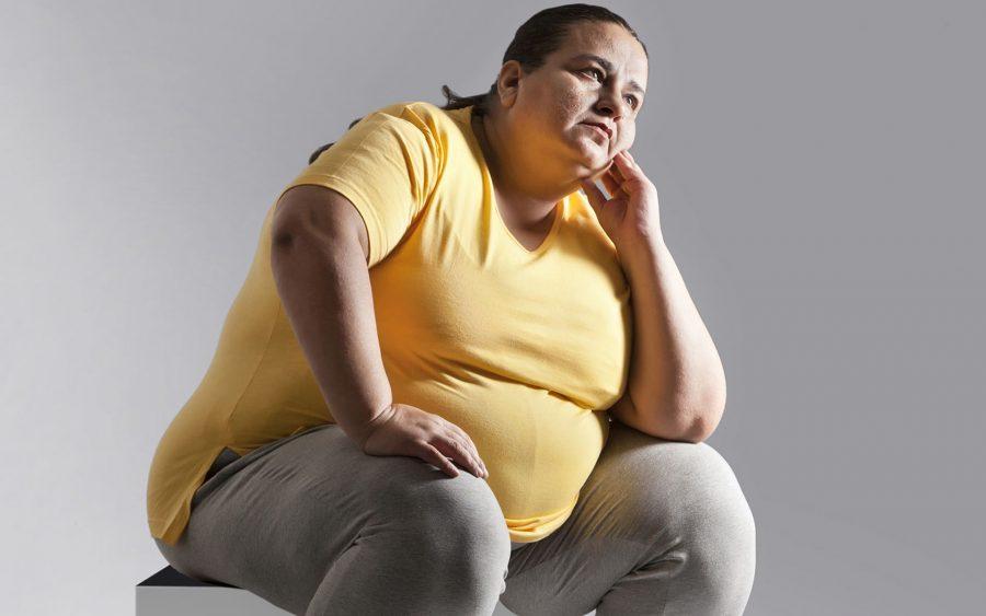 Толстая женщина сидит на диване