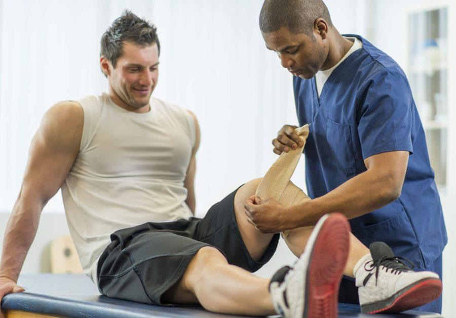 Спортивный врач разминает атлету колено на кушетке