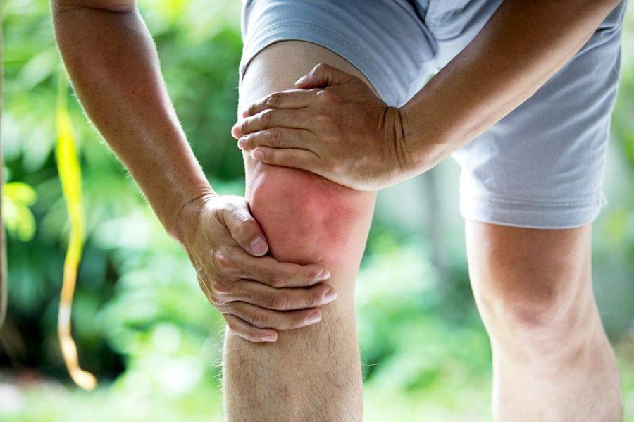 Боль в коленном суставе у мужчины в шортах