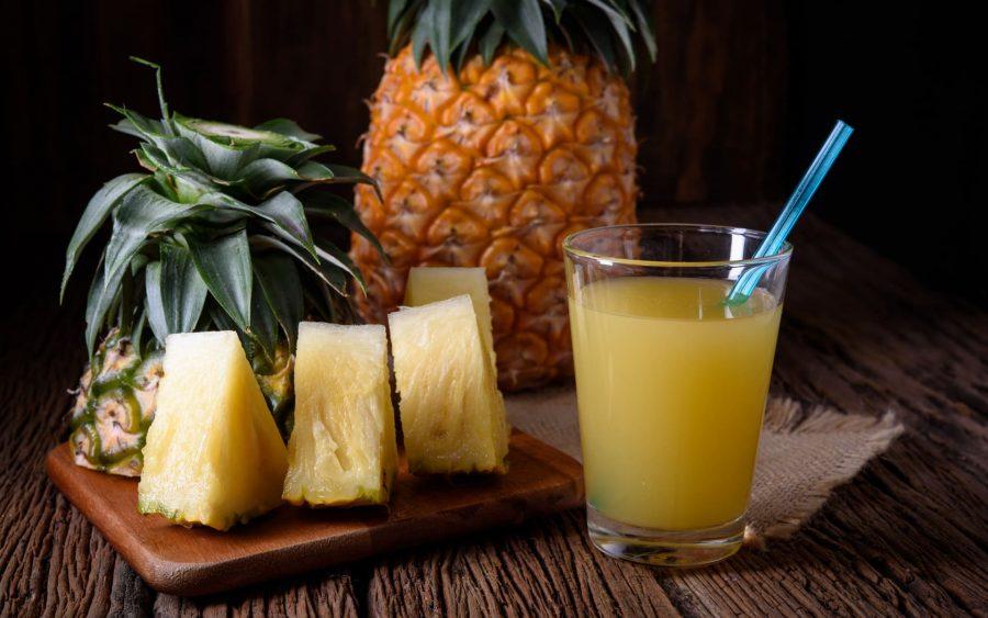Кусочки ананаса и сок ананасовый в стакане с трубочкой