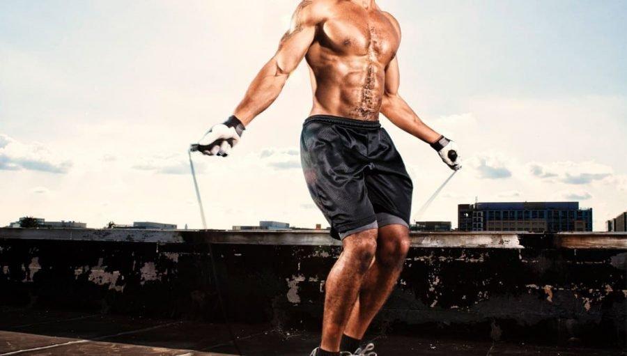 Спортсмен-культурист прыгает на скакалке