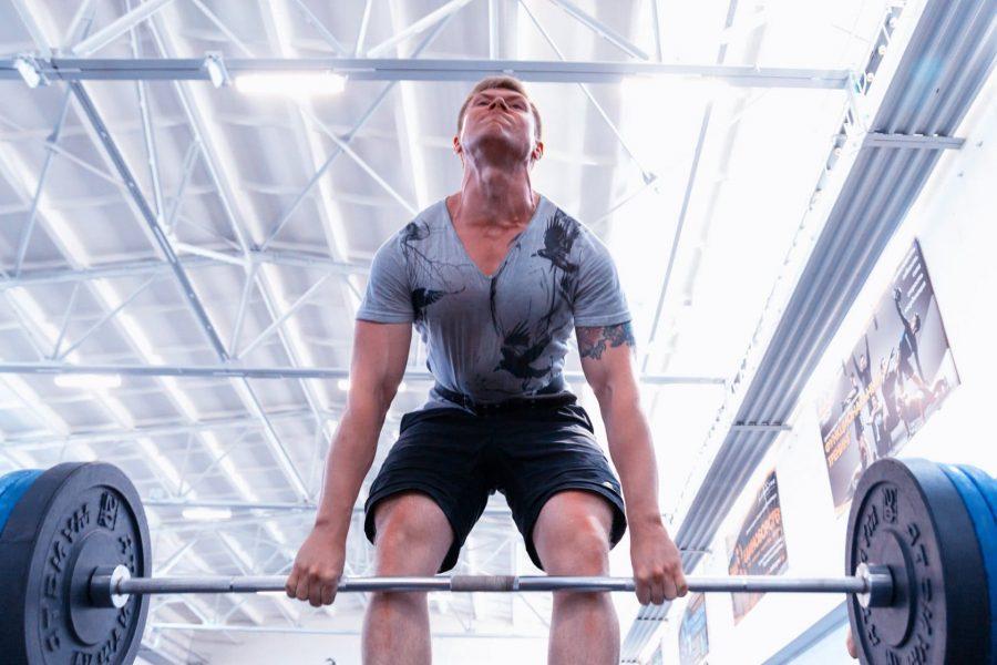 Парень выполняет тяжелую становую тягу с узкой постановкой ног