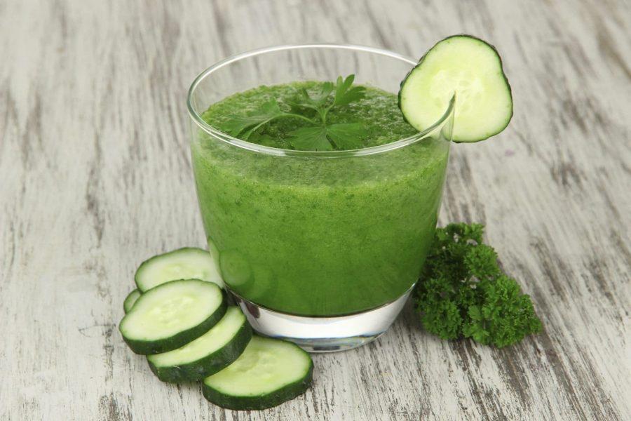 Стакан с огуречным соком и ломтик огурчика с зеленью