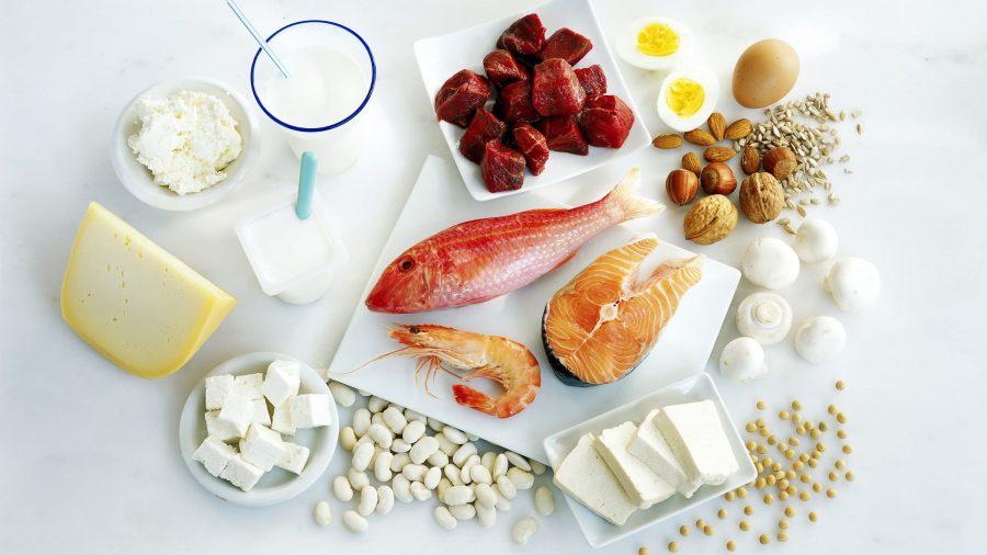 Красная рыба, мясо, яйца, творог, орехи сыр и молоко на светлом фоне