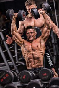 МУскулистые парни выполняют упражнения на плечи с гантелями