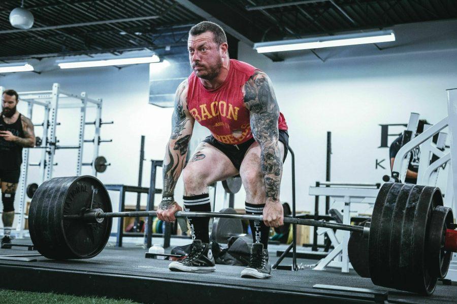 Татуированный атлет выполняет тяжелую становую тягу с узкой постановкой ног