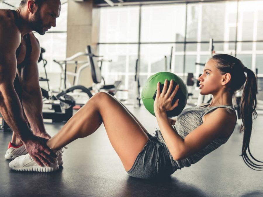Девушка выполняет упражнение на пресс с помощью партнера