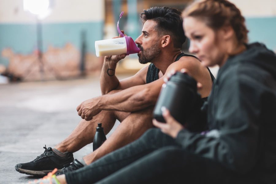 Парень и девушка употребляют сидя на полу тренажерного зала углевода-белковый коктейль