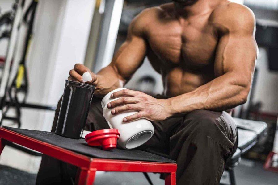 Атлет сидя на скамье в тренажерном зале употребляет спортивное питание