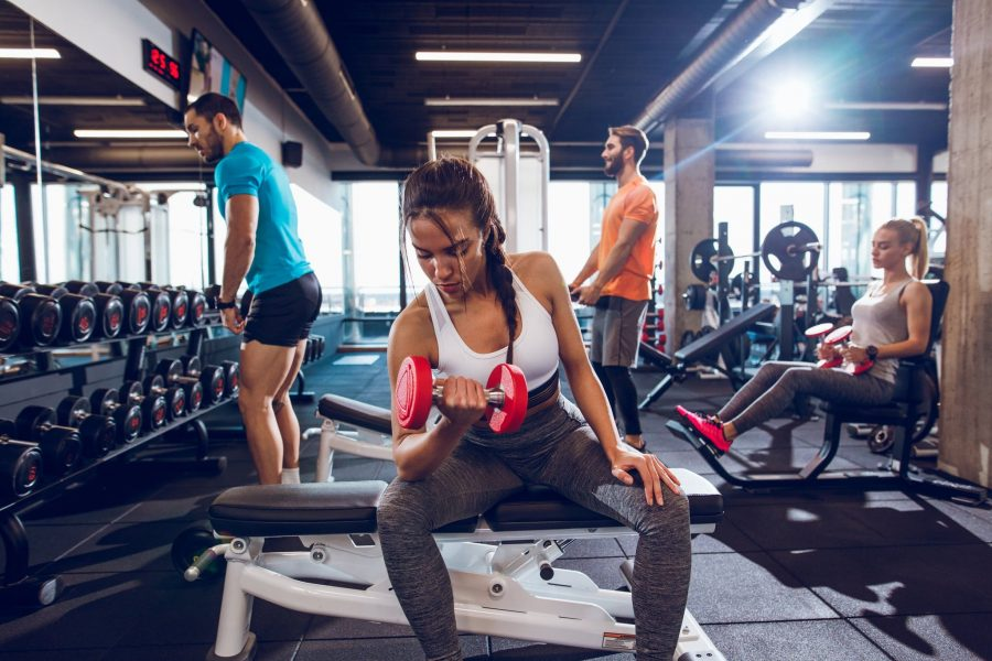 Парни и девушки в тренажерном зале выполняют упражнения