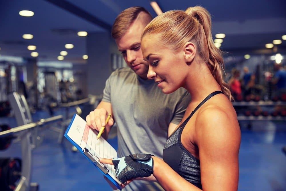 Девушка с тренером заполняют тренировочный дневник