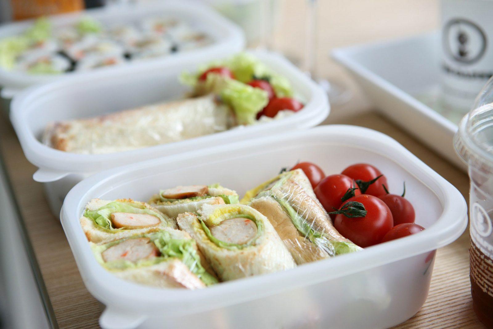 Контейнер с продуктами питания: фаршированные блины, помидоры, салат