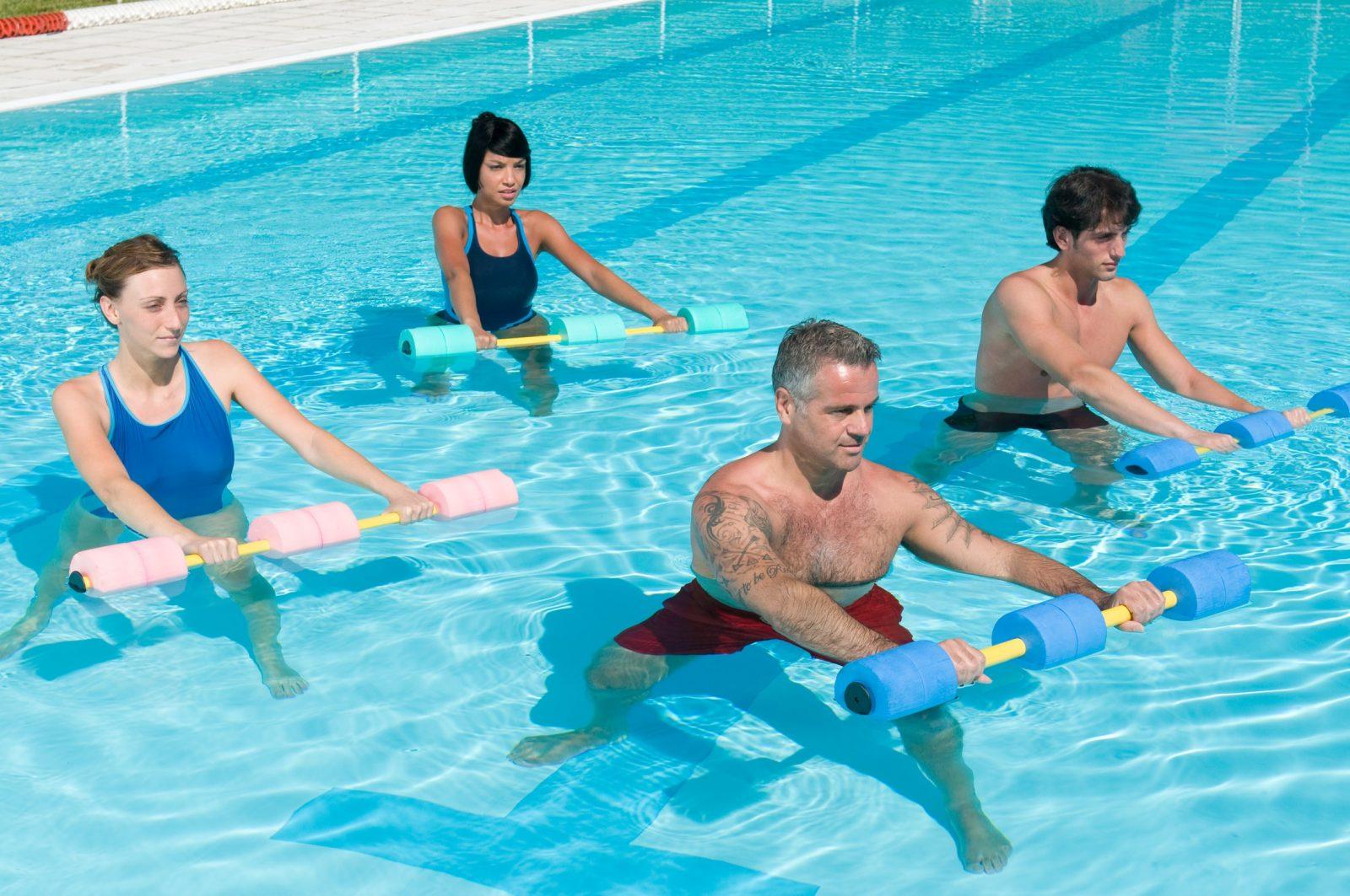 Мужчины и женщины занимаются фитнесом в бассейне