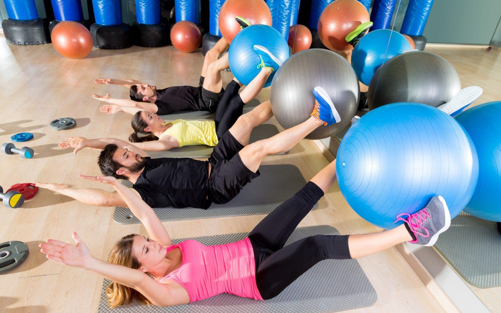 Девушки в спортзале делают упражнения с фитболом
