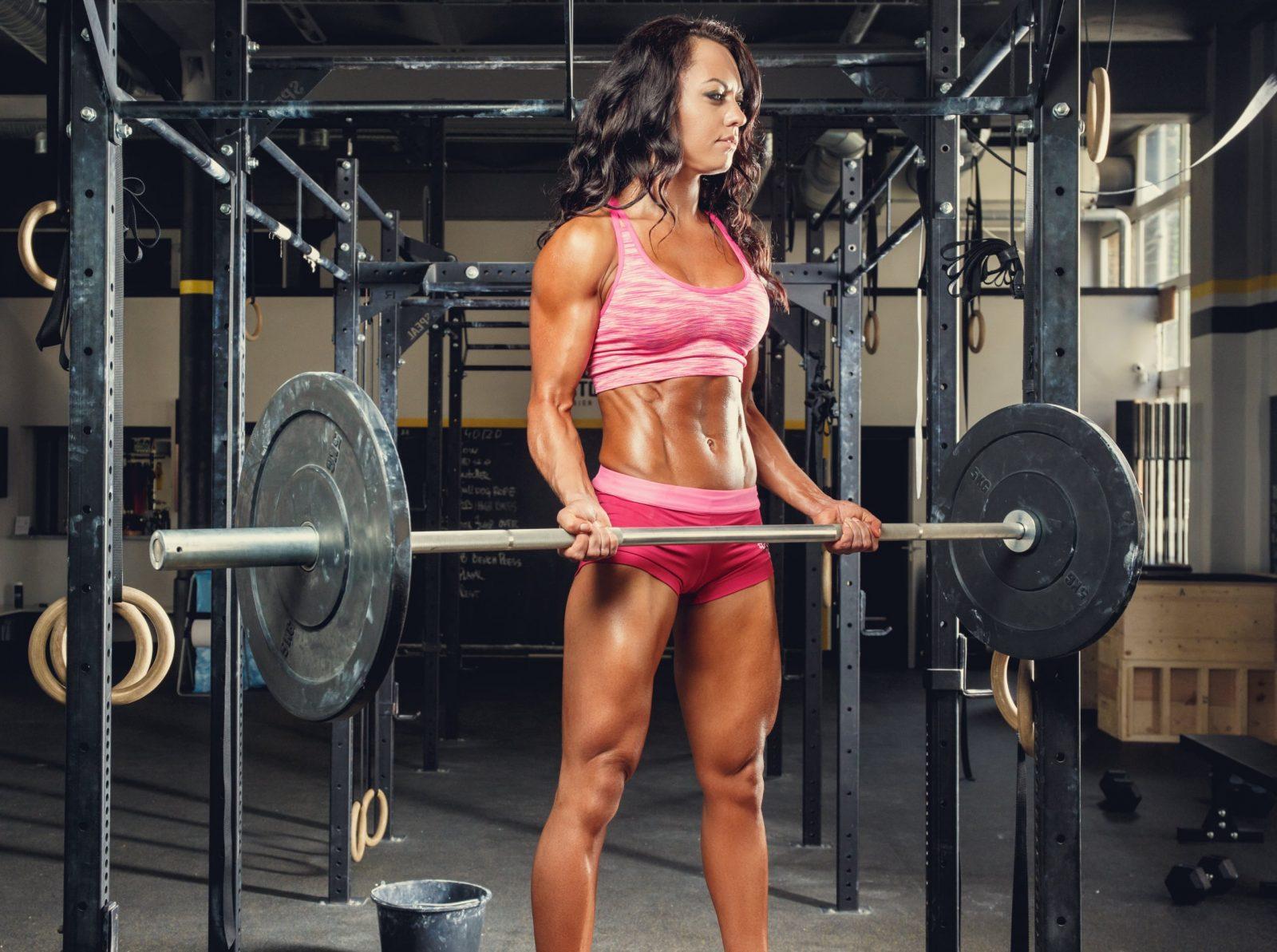 Девушка поднимает штангу на бицепс в тренажерном зале