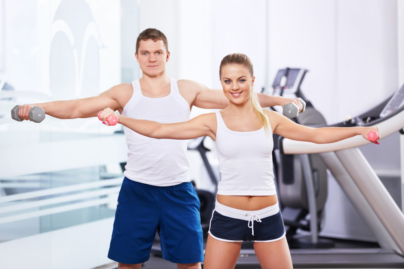 Спортивные девушка и парень выполняют упражнение с легкими гирями в тренажерном зале