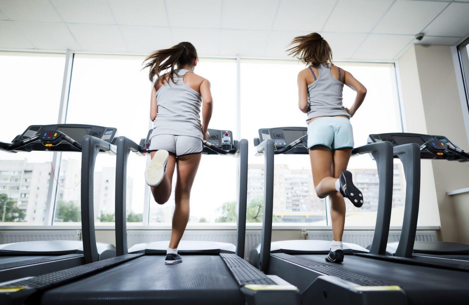 Две девушки в спортзале выполняют пробежку на беговой дорожке