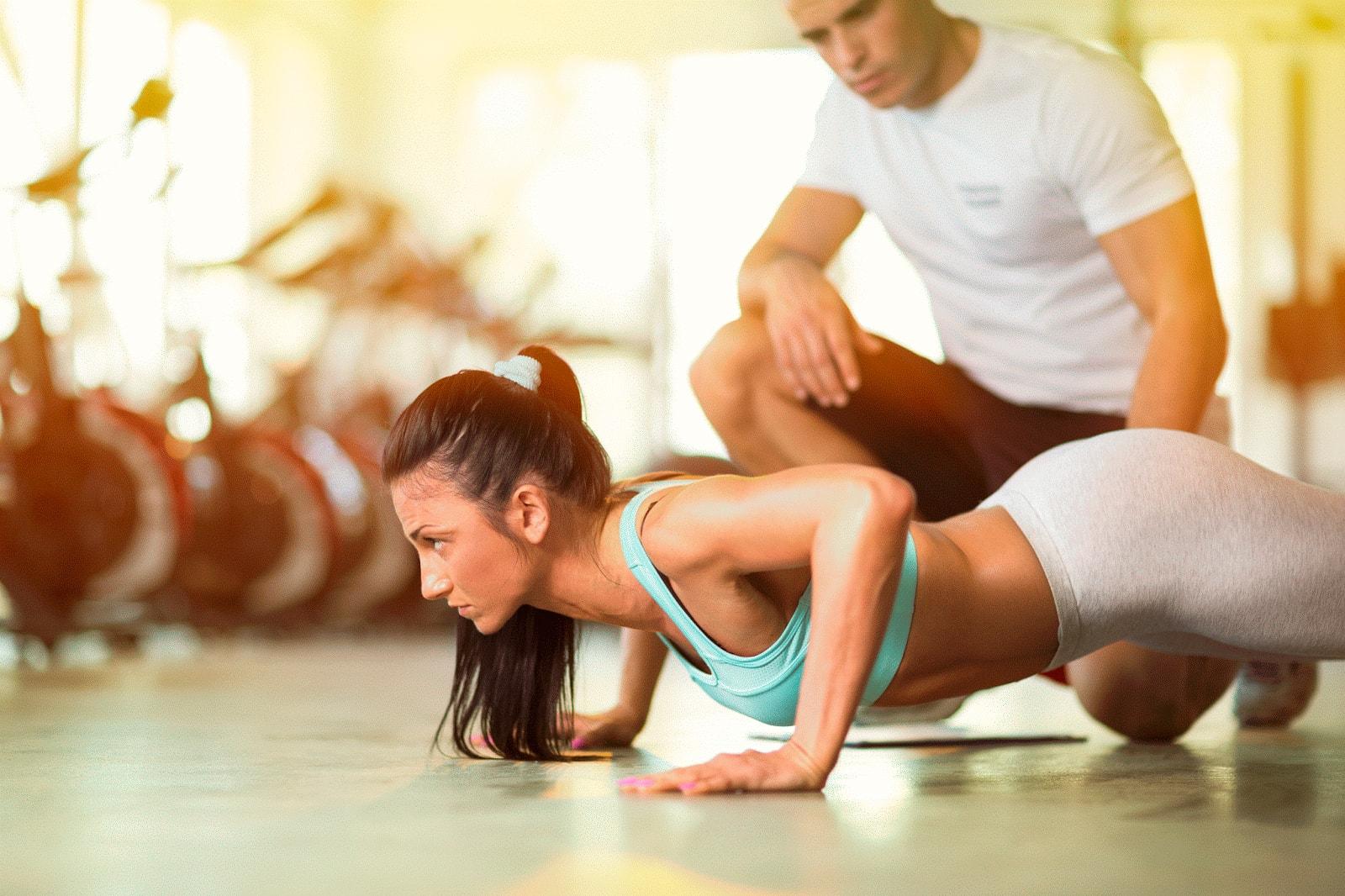 Спортивная девушка отжимается от пола под присмотром тренера
