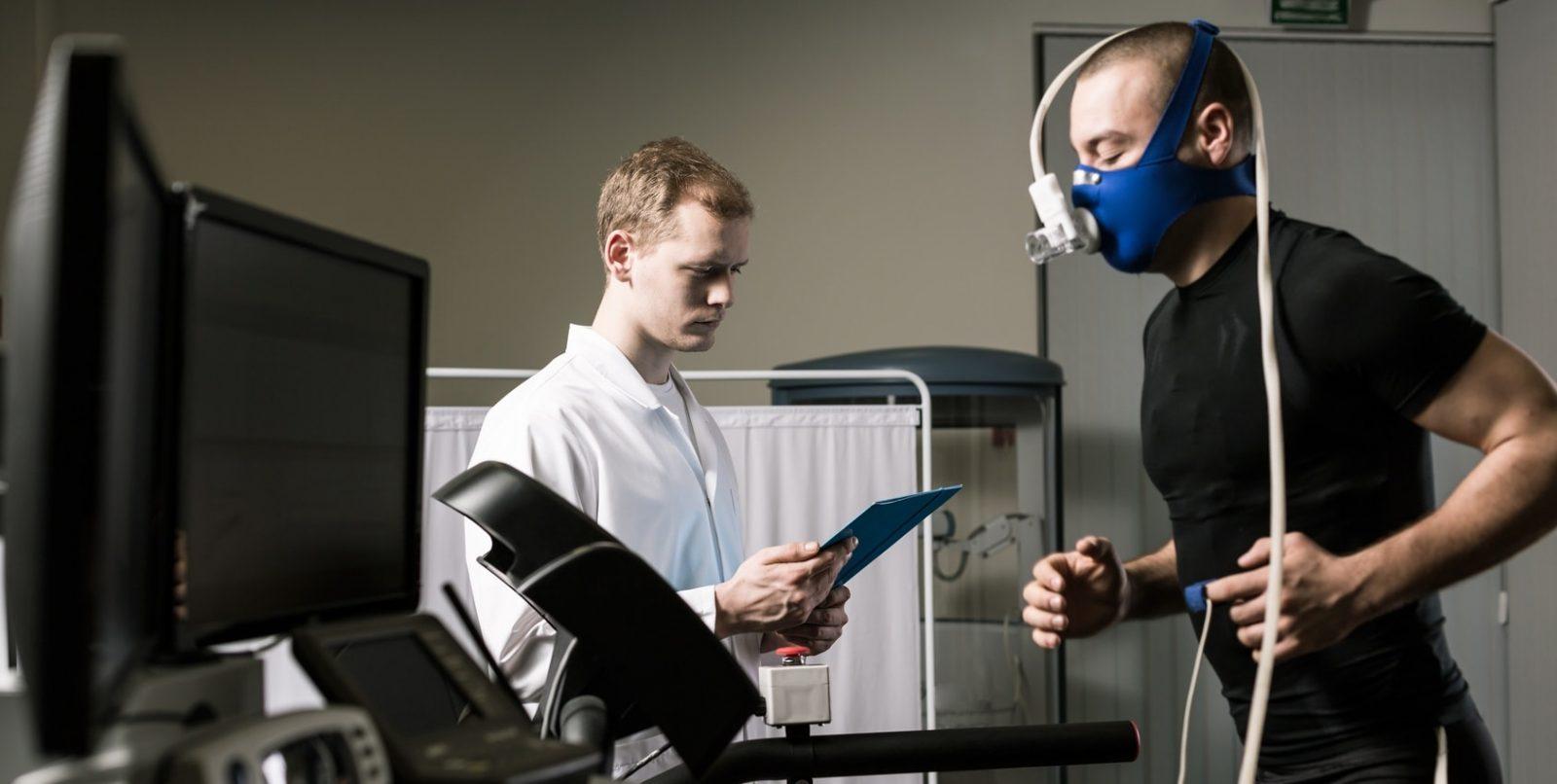 Врач контролирует дыхательные параметры (расход кислорода) в теле спортсмена, который бежит на беговой дорожке в специальной маске