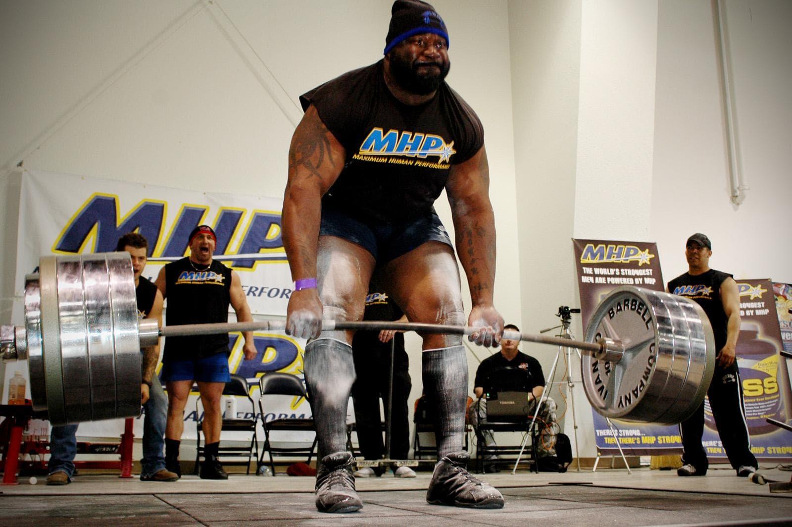 Бородатый атлет пауэрлифтер выполняет тяжелую становую тягу