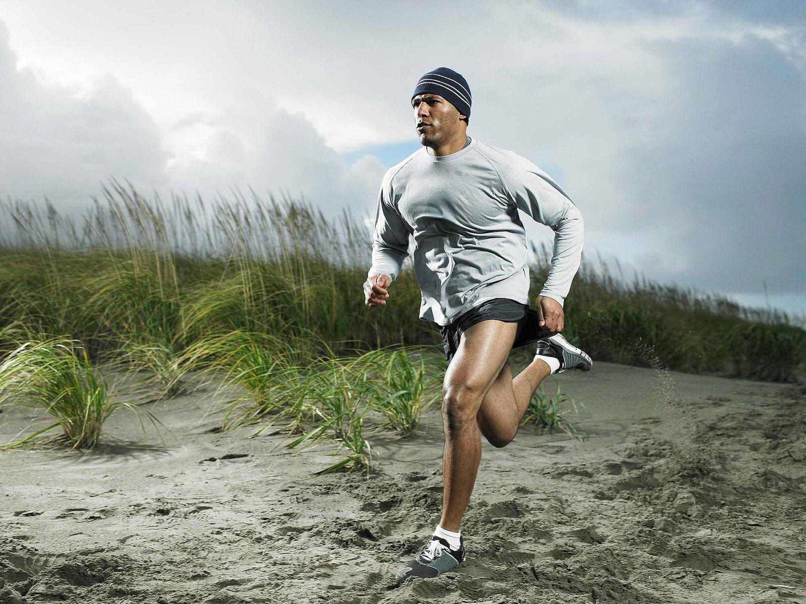 Спортсмен бежит по песку в светлой толстовке и шапке