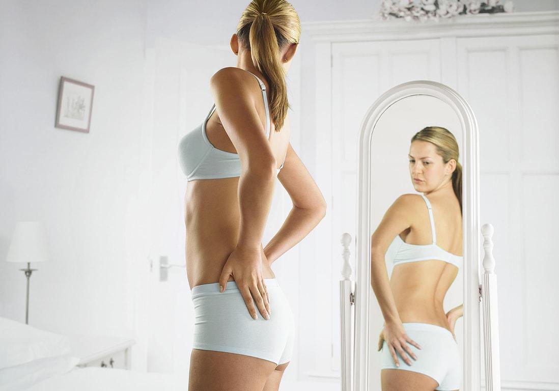 Девушка в нижнем белье смотрится в зеркало
