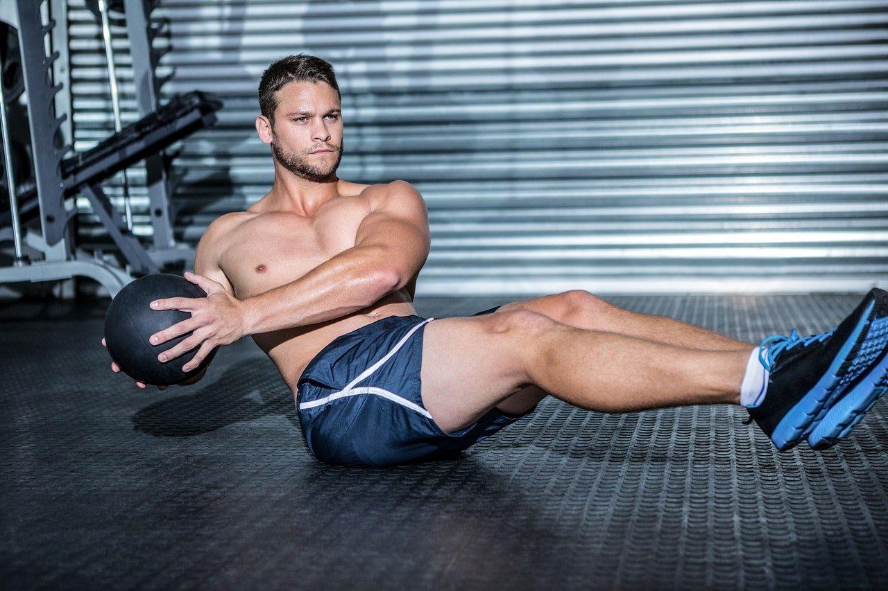 Накаченный парень на полу выполняет упражнение с медболом (медицинским мячом)