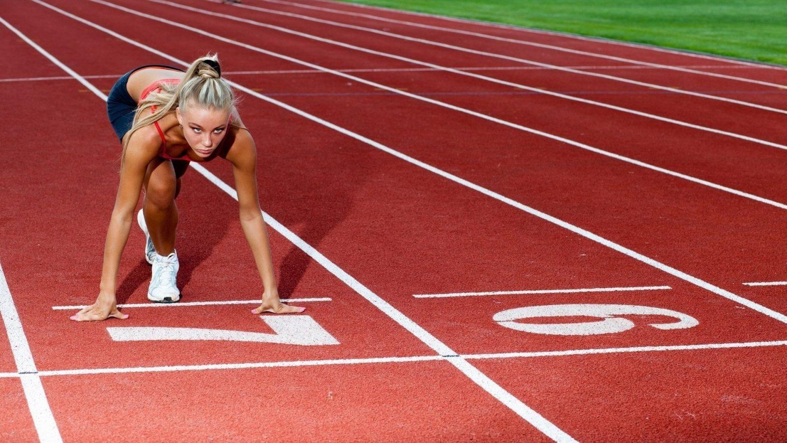 Красивая, спортивная девушка на беговом стадионе