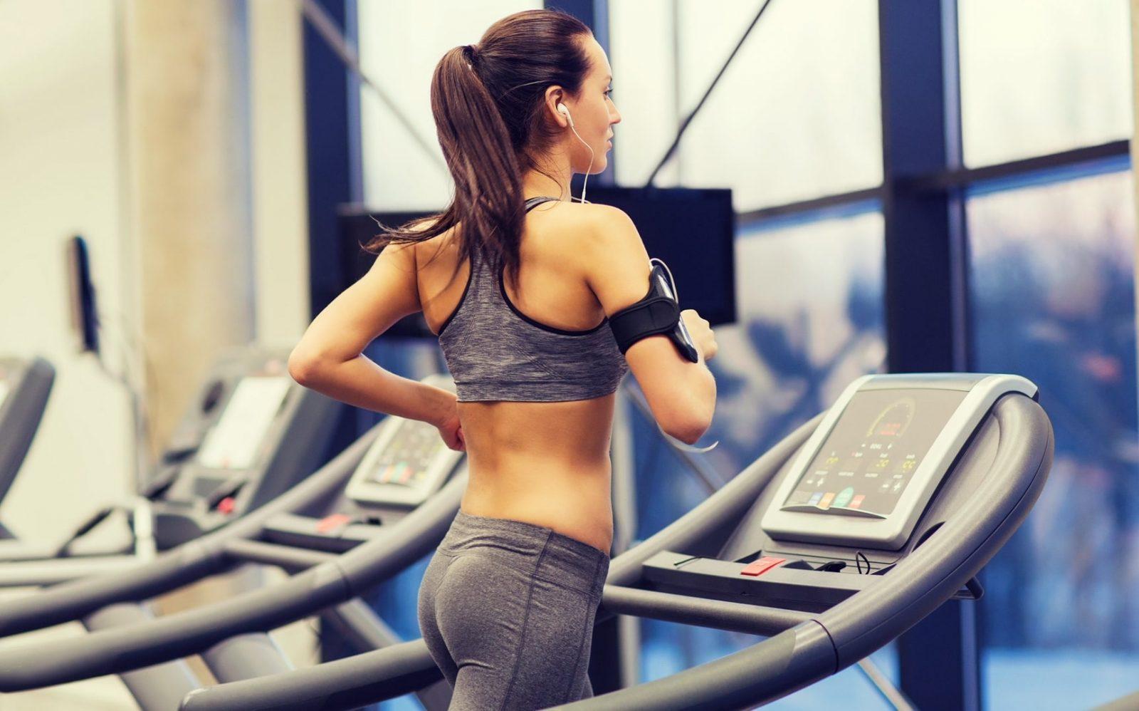 Спортивная девушка в наушниках занимается на беговой дорожке