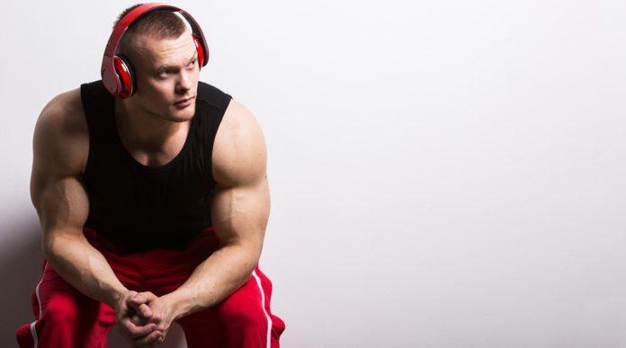 Накаченный атлет в безрукавке слушает музыку надев красные наушники