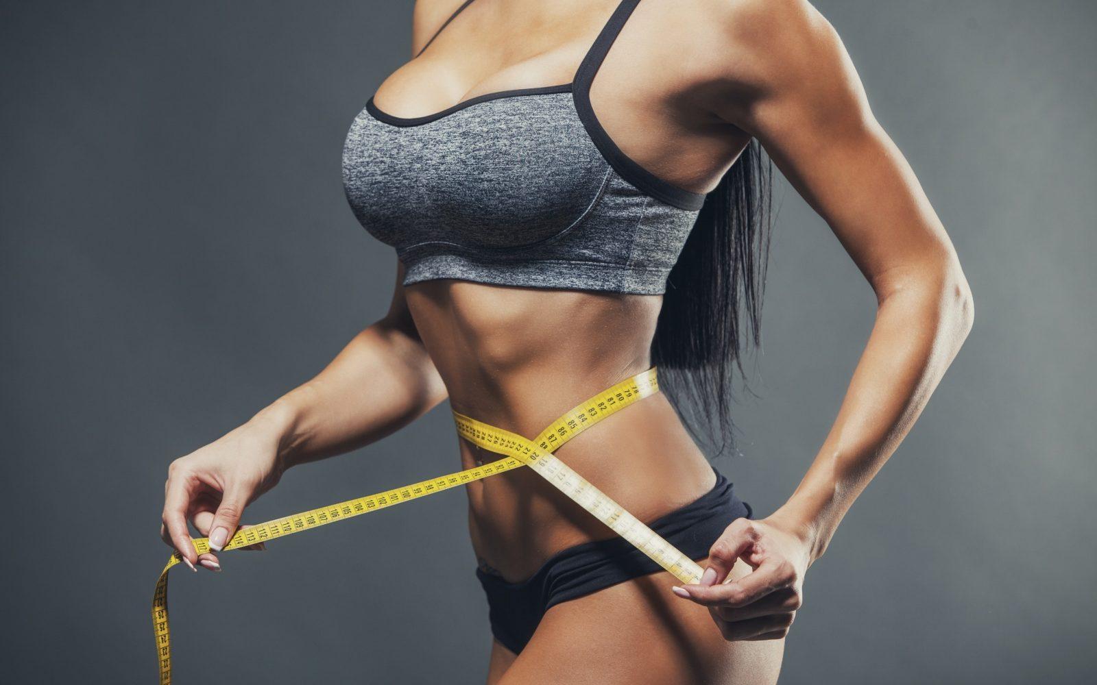 Спортивная девушка с плоским животом измеряет сантиметровой лентой свою стройную талию