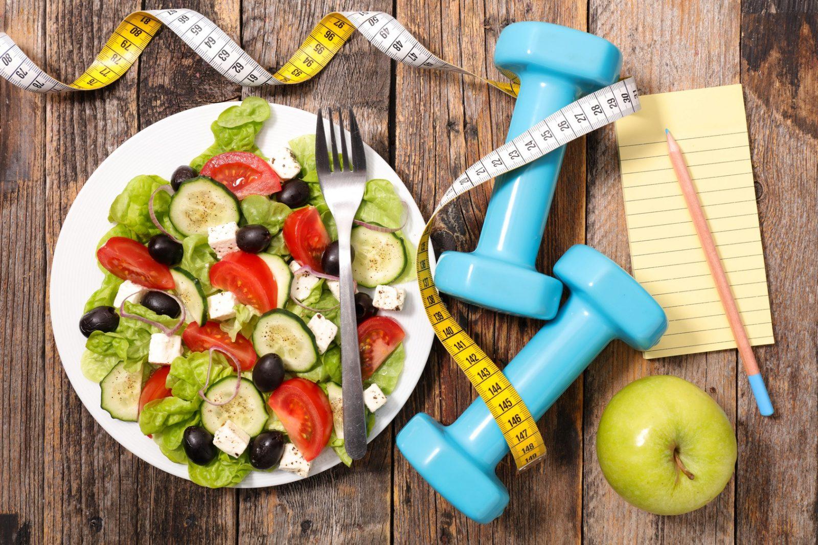 Салат, яблоко зеленное, сантиметровая лента и легкие гантели голубые