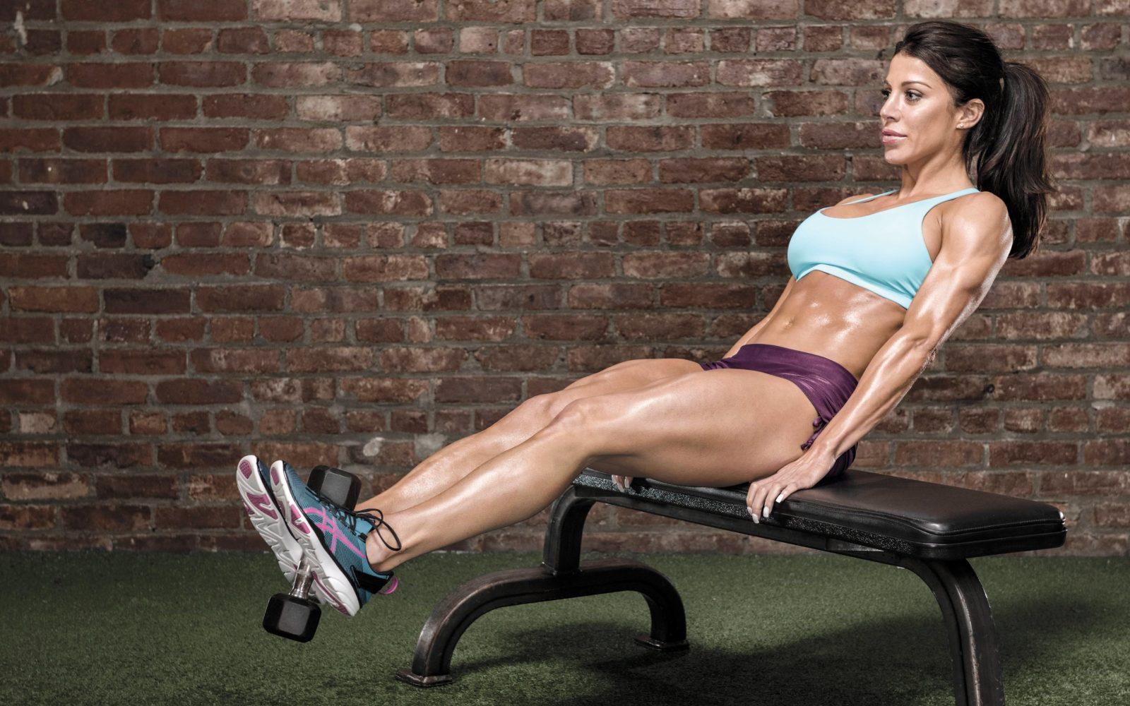 Девушка на скамье поднимает ноги с гантелью