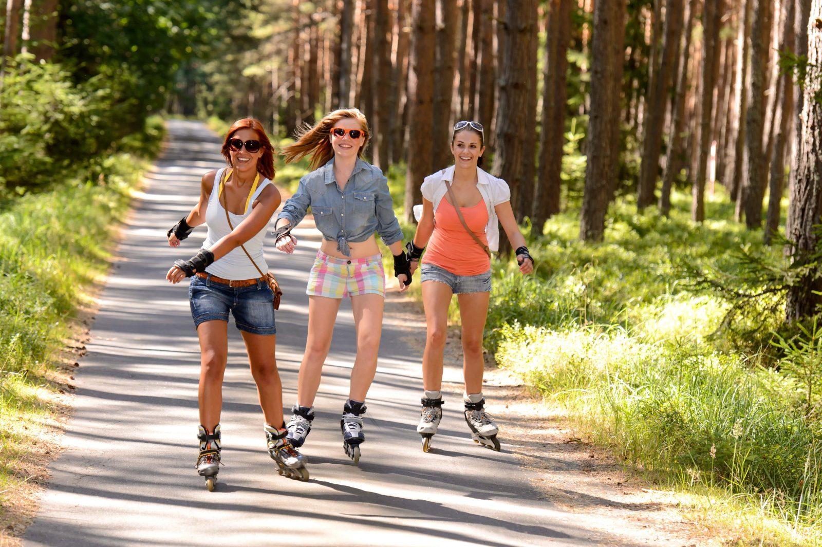 Три девушки катаются за городом на роликах