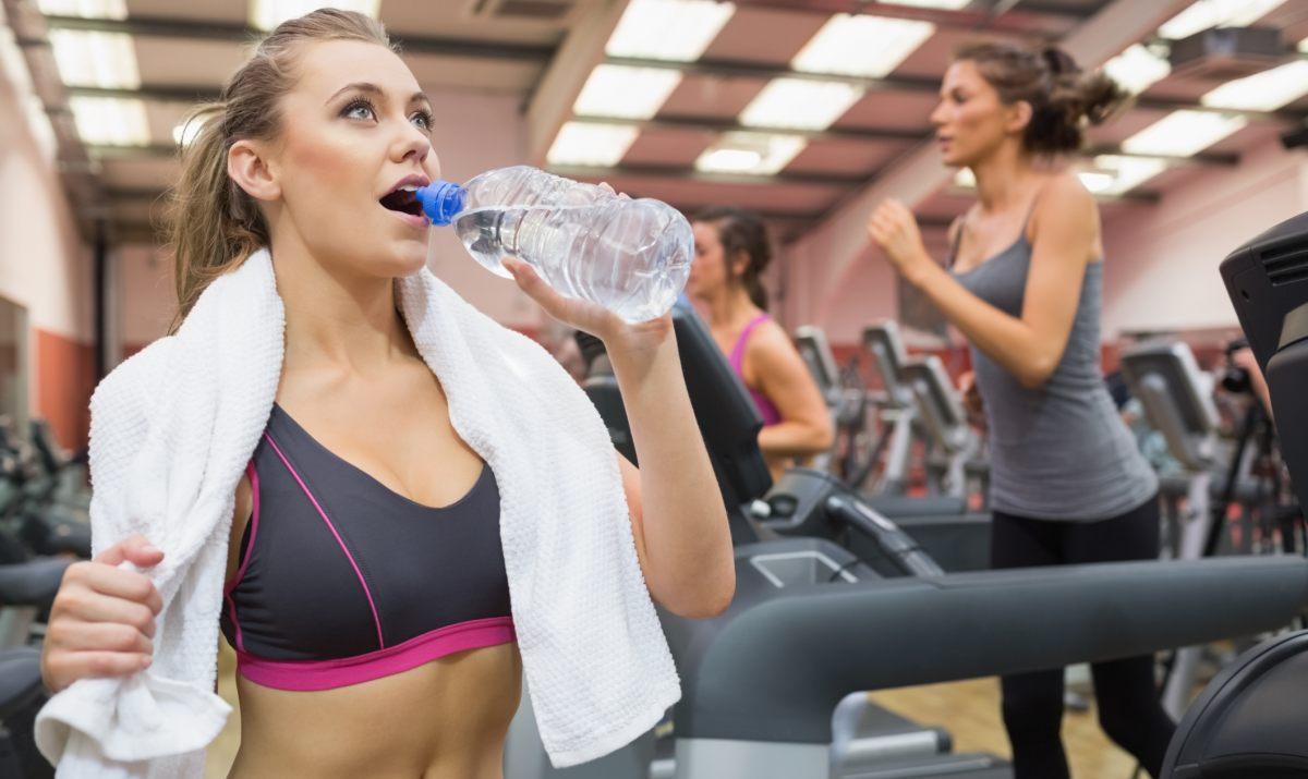 Девушка пьет чистую воду из бутылки в тренажерном зале