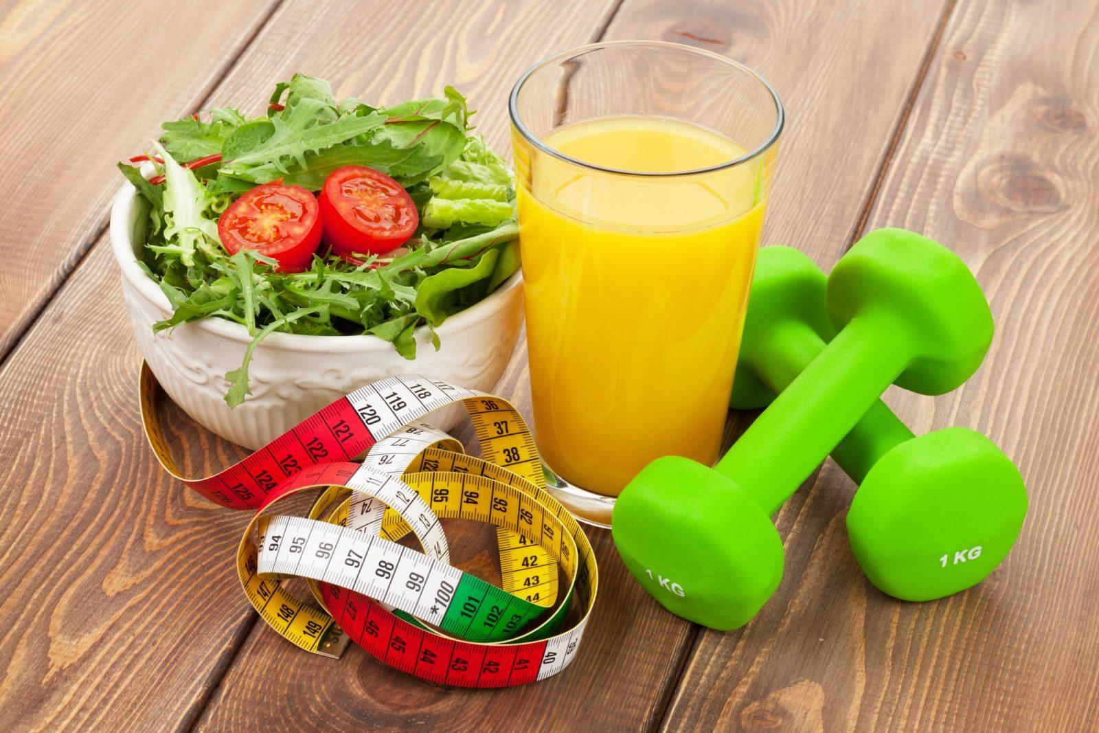 Стакан апельсинового сока, сантиметровая лента, зеленый салат с помидорами, зеленные гантели