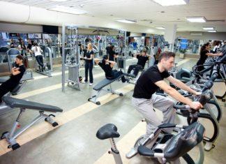 Парни и девушки выполняют упражнения в тренажерном зале