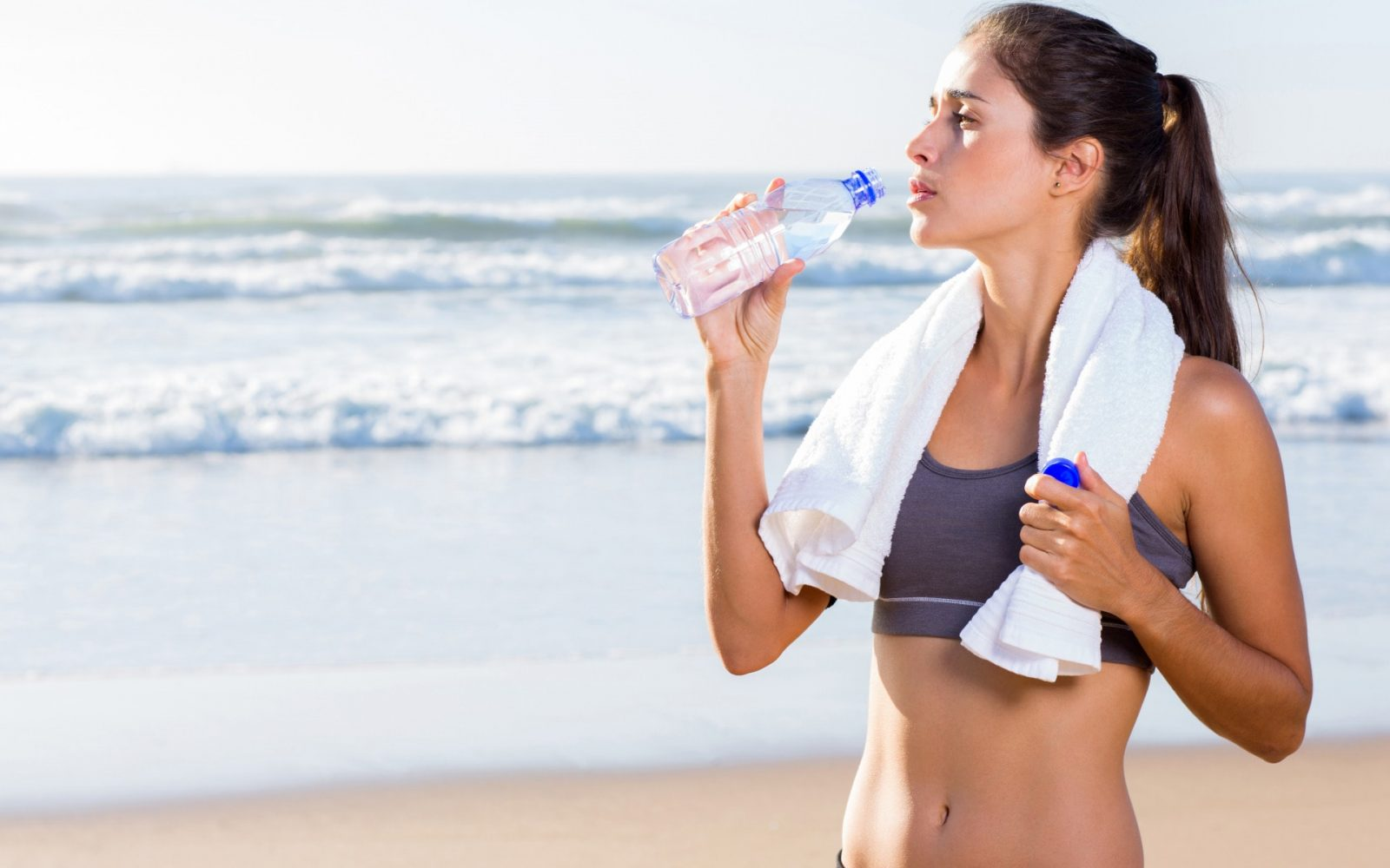 Девушка на берегу море с полотенцем на шеи и голым пузом пьет чистую воду из бутылке