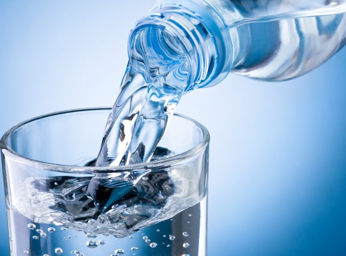 Чистую воду наливают в прозрачный стакан на голубом фоне