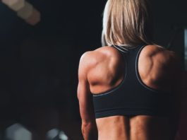 Спортивная девушка в черном топе демонстрирует мышцы спины
