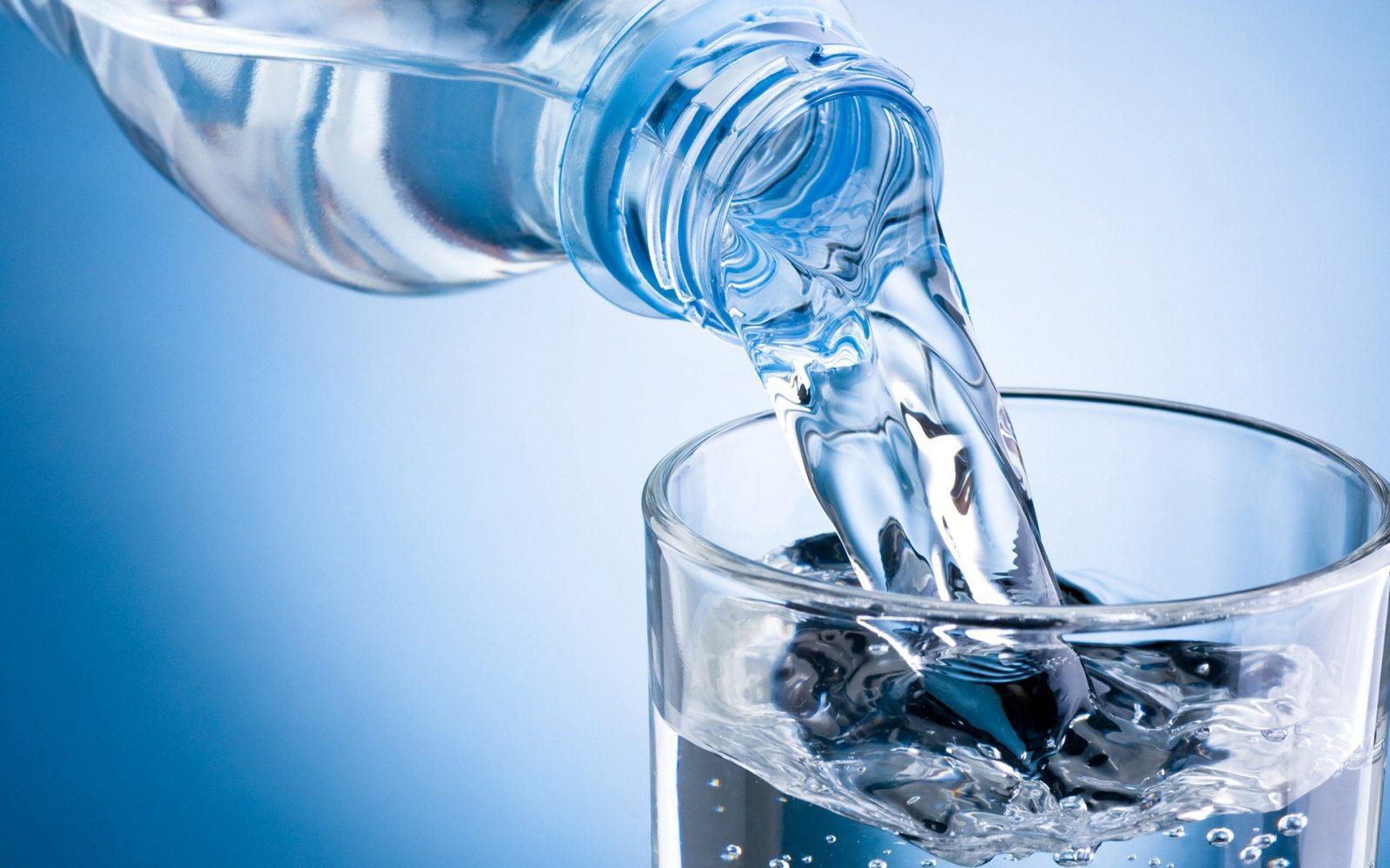 Минеральная вода наливается в прозрачный стакан