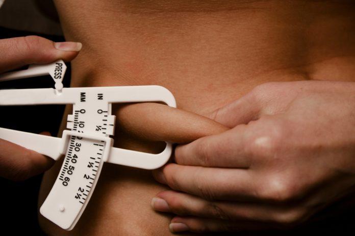Девушка измеряет процент жира в организме