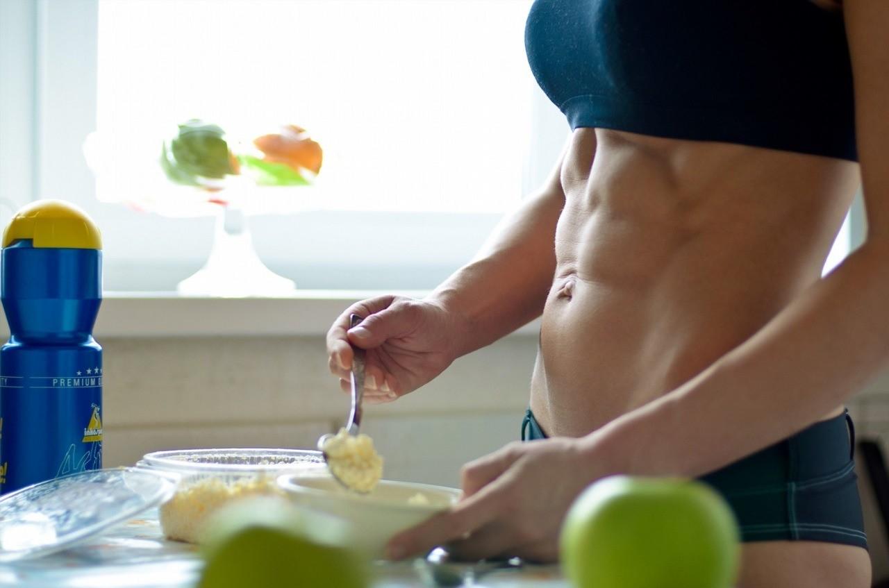 Спортивная девушка на кухне готовит продукты питания