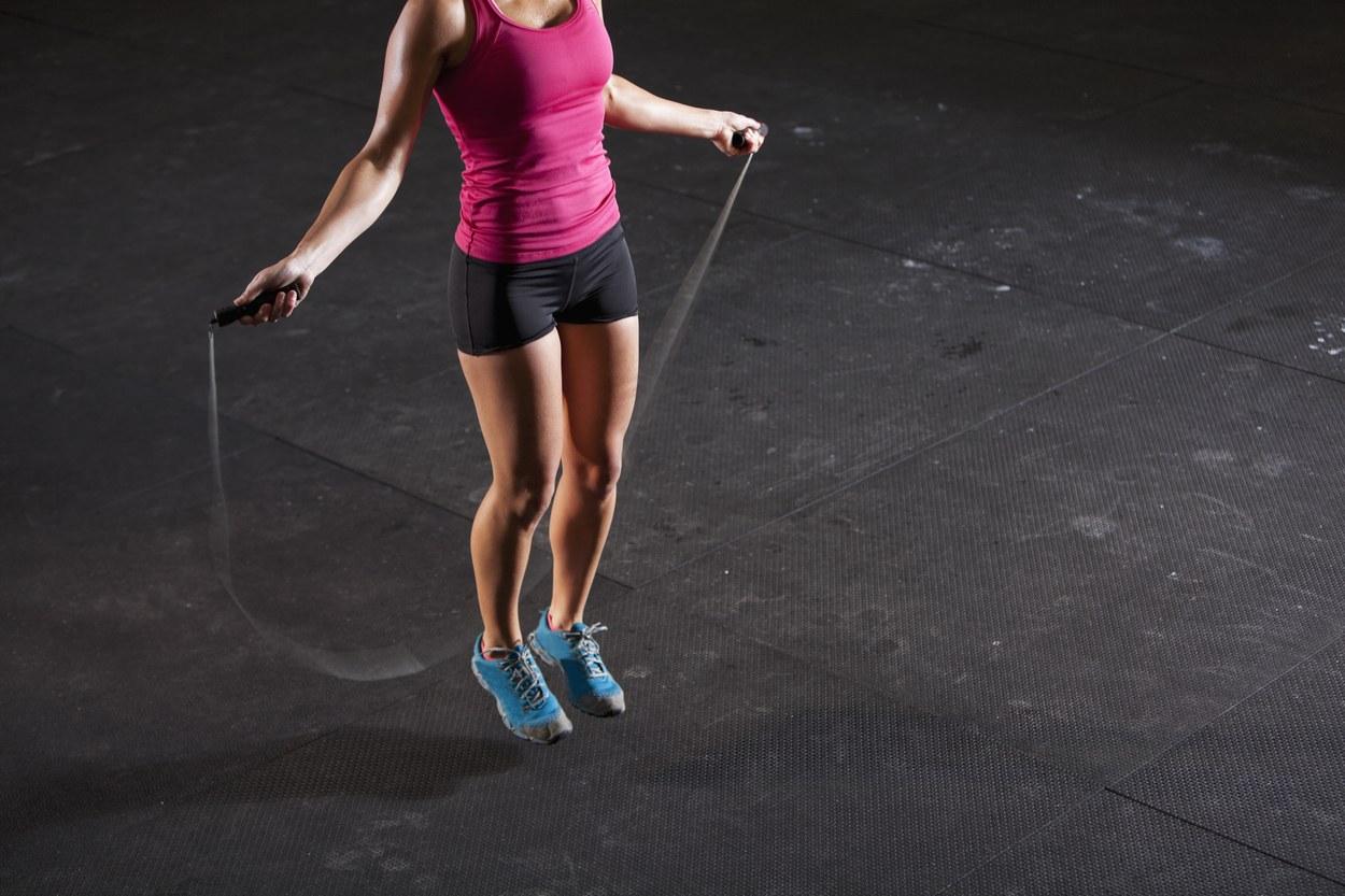 Девушка выполняет прыжки на скакалке