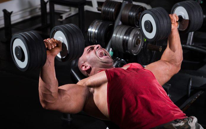 Опытный атлет в тренажерном зале выполняет упражнение: жим гантелей лежа на наклонной скамье