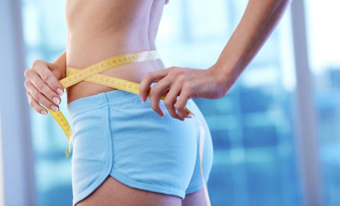 Стройная девушка в голубых шортиках измеряет талию сантиметровой лентой