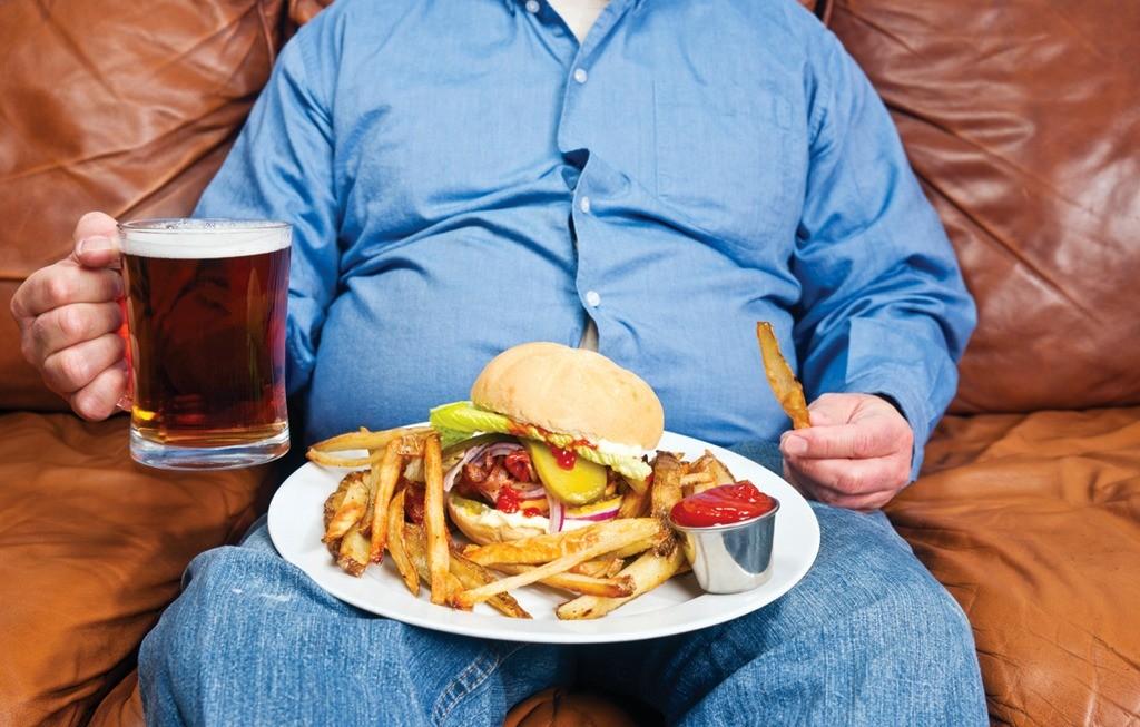 Толстый мужик пьет пиво на диване и ест вредные продукты