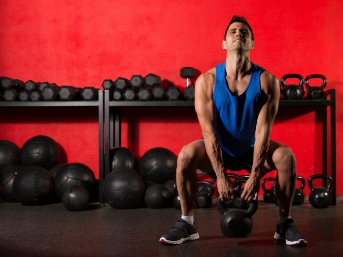 Атлет с гирей выполняет упражнение в тренажерном зале