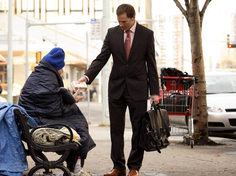 Мужчина в пиджаке делиться печеньем с бездомной старушкой