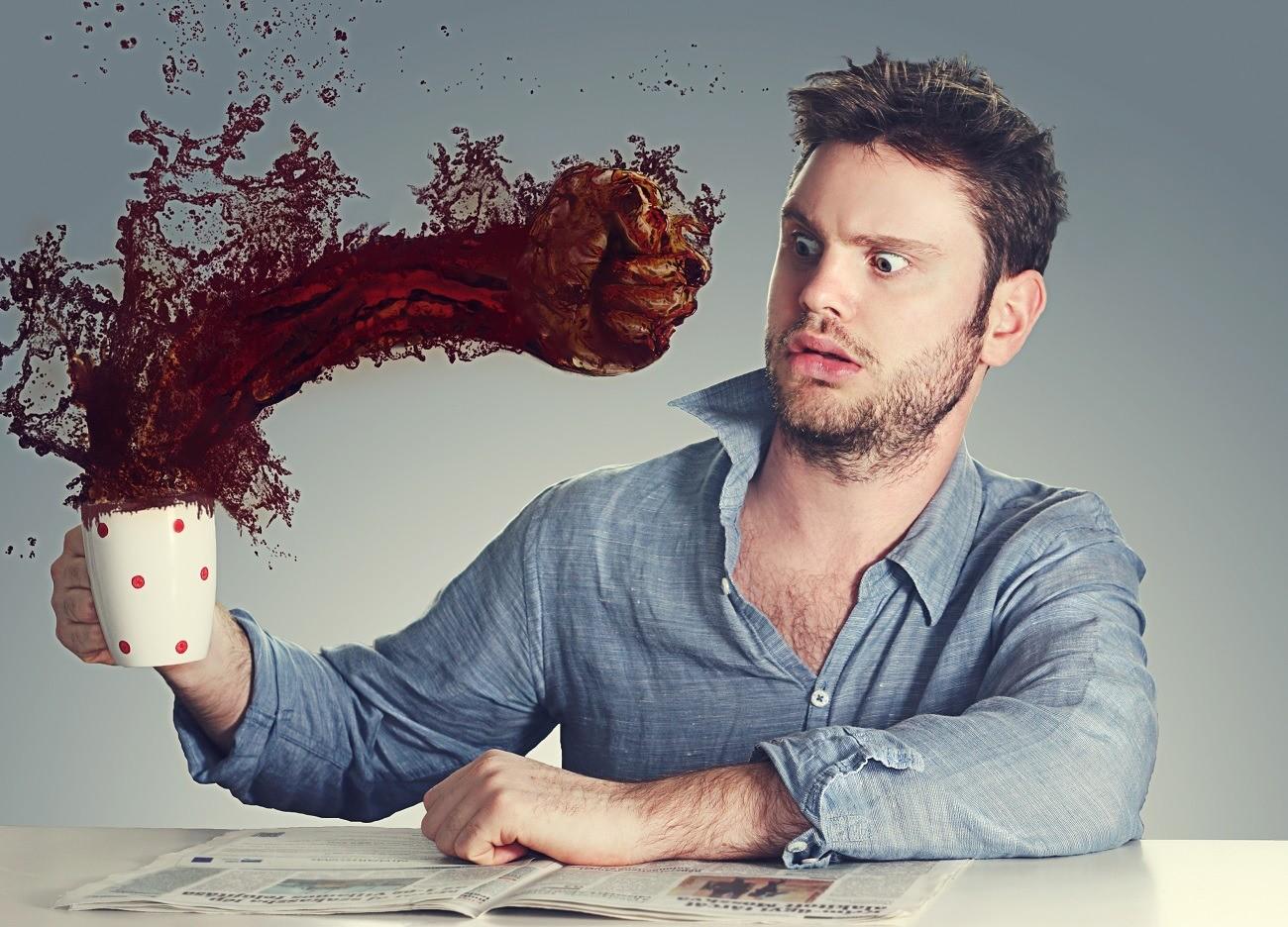 Чашка кофе фантастически ударяет кулаком мужчину